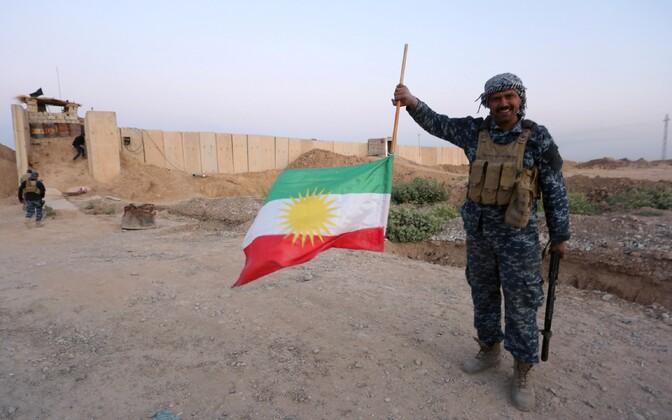 Иракский военный держит перевернутый курдский флаг.