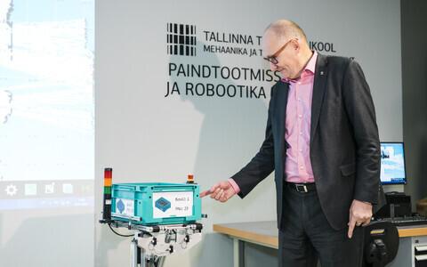TTÜ rektor Jaak Aaviksoo käivitamas robotit, mis automatiseerib tootmist ja automaatladustamist.