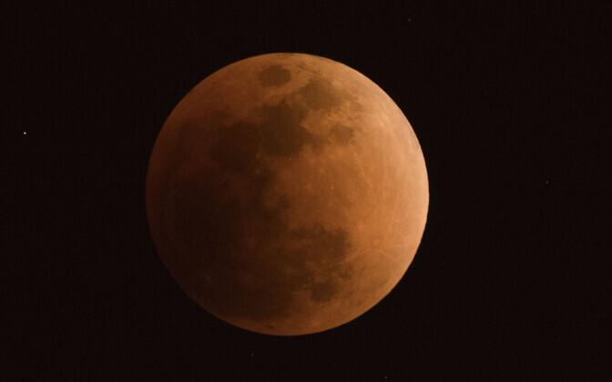 Kuu täisvarjutuse ajal Bejingi linnas. Kaaslasele lisab punakust piirkonna õhus leiduvad peenosakesed.