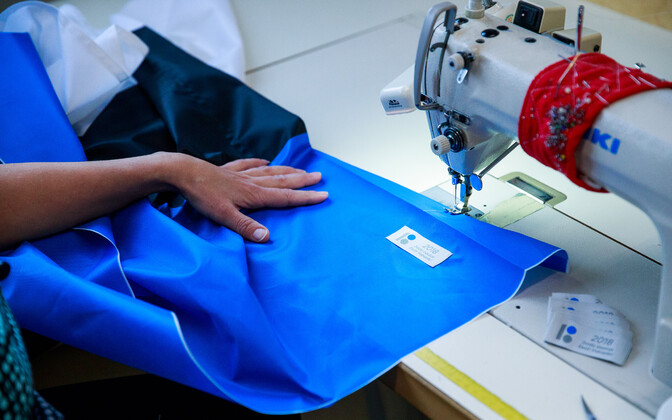 The sewing of a blue, black and white Estonian flag.