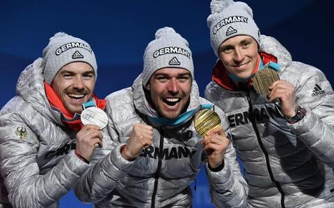 Sakslased Fabian Riessle, Johannes Rydzek ja Eric Frenzel tähistavad pjedestaalil kahevõistluse kolmikvõitu