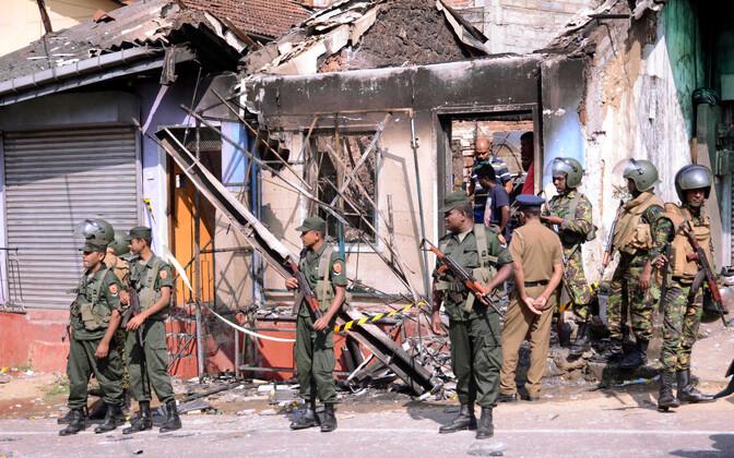 Sri Lanka eriüksuslased Kandy regioonis Diganas kokkupõrgete käigus põlema pandud hoone ees.