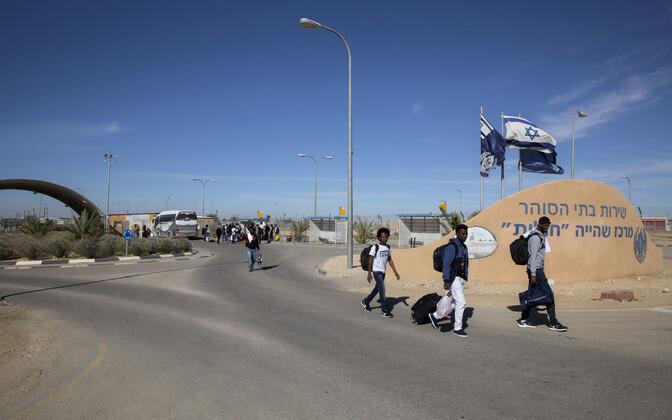 Aafriklastest migrandid lahkumas Holoti kinnipidamiskeskusest Negevi kõrbes.
