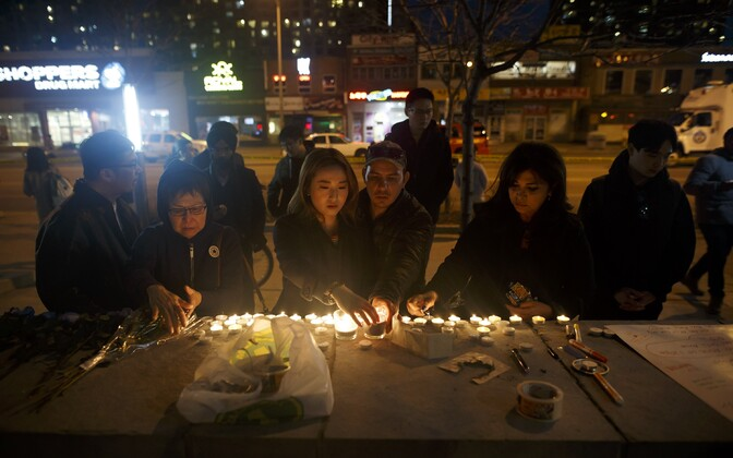 Люди зажигают свечи в память о жертвах наезда фургона на пешеходов в Торонто.