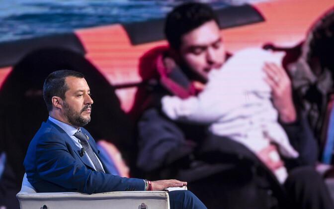 Itaalia siseminister Matteo Salvini, taustaks Vahemerelt päästetud migrantide foto.