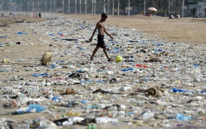 India poiss jalutab läbi plastikuga kaetud ranna Mumbais.