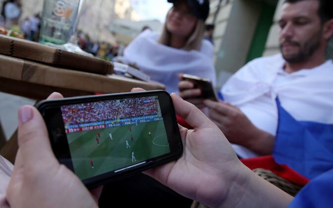 Jalgpallifännid telefonist mängu vaatamas.
