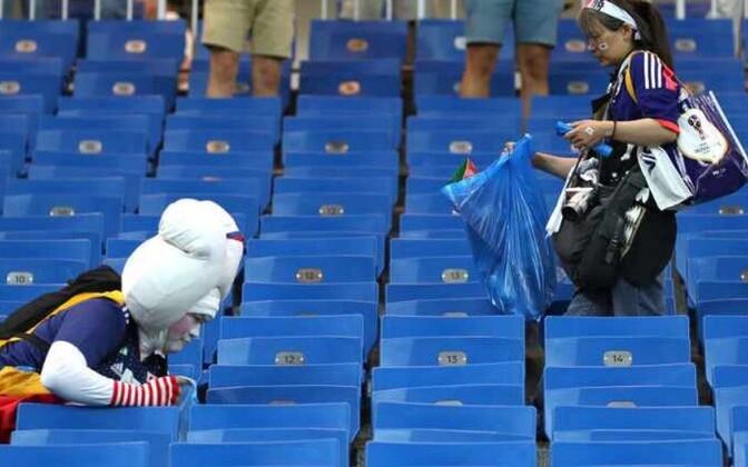 Японские болельщики после матча убирают трибуны.