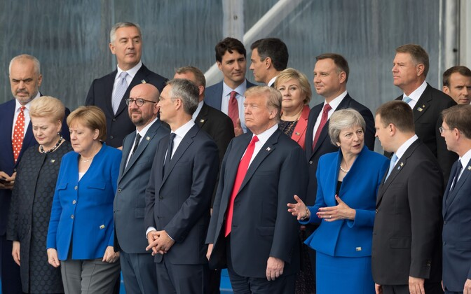Estonian and British Prime Ministers chat at the NATO summit, next to Donald Trump.