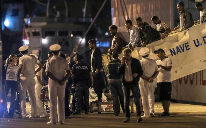 Мигранты сходят на берег в Италии.