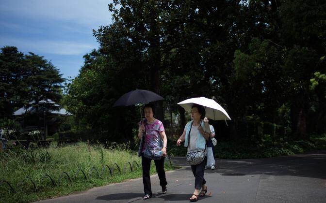 Tokyo naised end päikese eest varjamas.