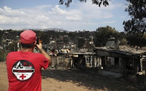 Спасатель фотографирует последствия пожара в городке Мати.