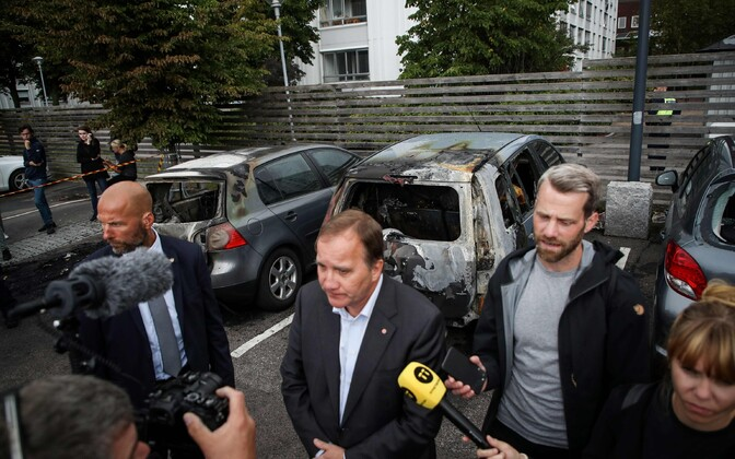 Rootsi peaminister Stefan Löfven räägib ajakirjanikega põlenud autode juures Göteborgis.