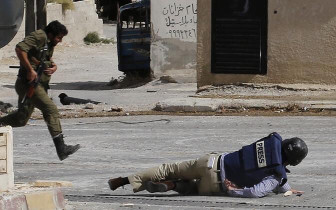 Kirja autor AFP korrespondent Sammy Ketz 2013. aastal Süürias Maalula linnas snaiperpüssi kuulide eest maha viksumas.