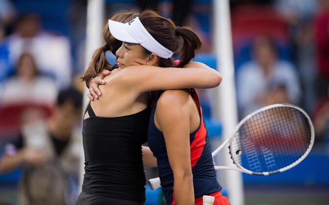 Kontaveit and Wang Qiang hug after the latter drops out of their semifinal match.