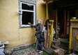Жительница поселка Дружба рассматривает разбитое в результате взрывов на оружейном складе окно своего дома.
