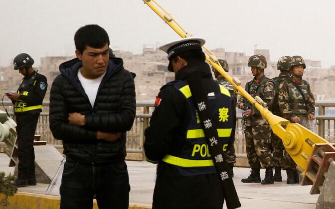 Hiina politseiametnik kontrollib uiguuri mehe dokumente.
