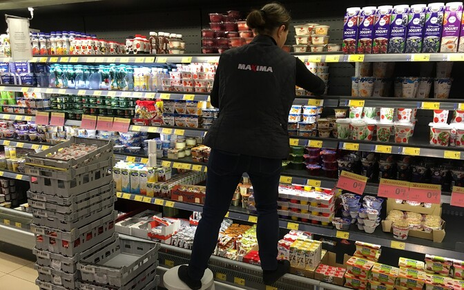 Employee restocking dairy goods at a Maxima grocery store.