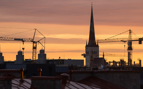 Construction cranes in Tallinn with St. Olaf's Church visible in the background.