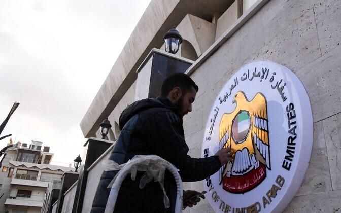 Чистка эмблемы на стене посольства ОАЭ в Дамаске.