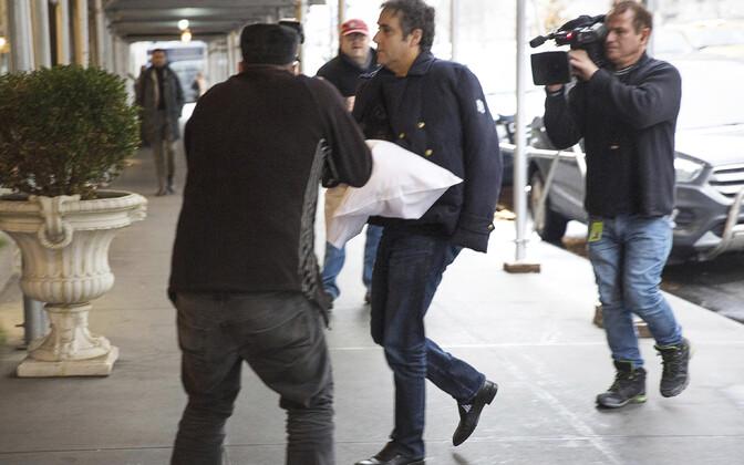 Michael Cohen ilmusl oma New Yorgi kodu juurde veidralt padjaga kätt toetades.
