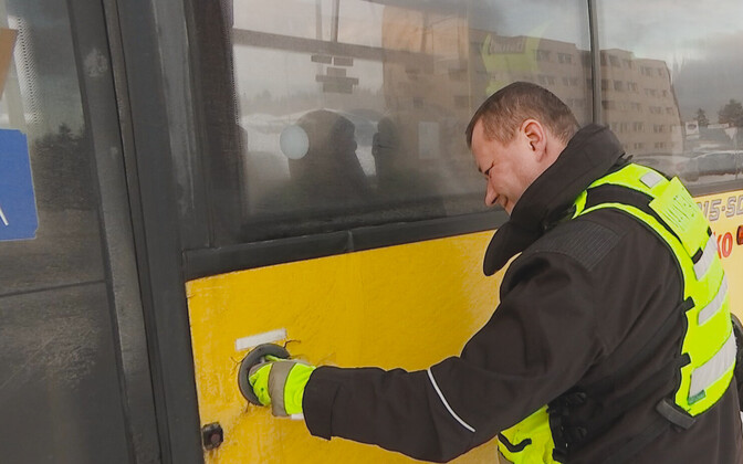 Police officer inspecting an Atko bus.