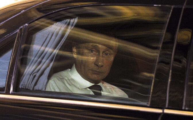Venemaa president Vladimir Putin ametiauto aknast välja vaatamas.