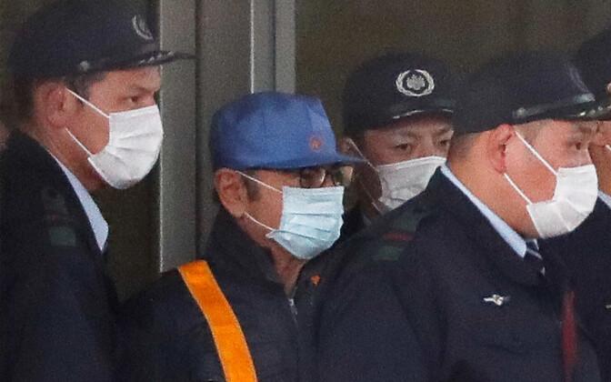 Carlos Ghosn (helesinise mütsiga) lahkumas 6. märtsil Tokyo eeluurimisvanglast.