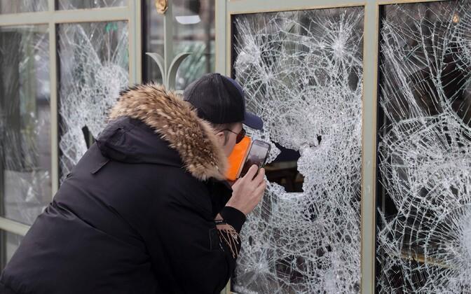 Mööduja Champs-Elysees'l purunenud poeaknent pildistamas.