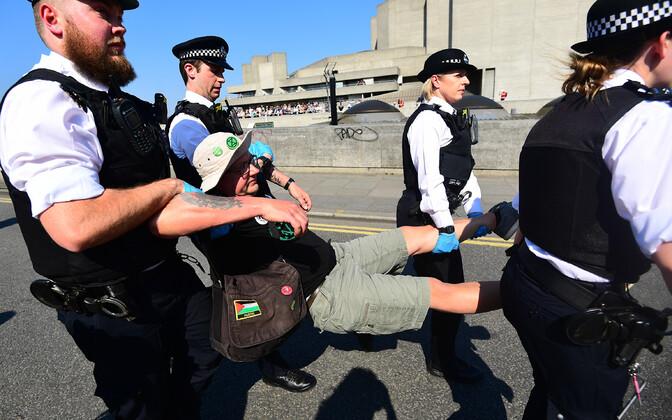 Politsei vedamas kliimaprotestijat Waterloo sillal.