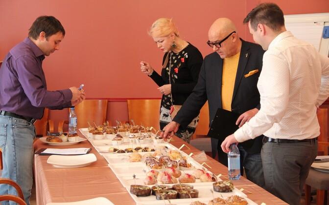 Члены экспертной комиссии пробуют различные кондитерские изделия во время конкурса