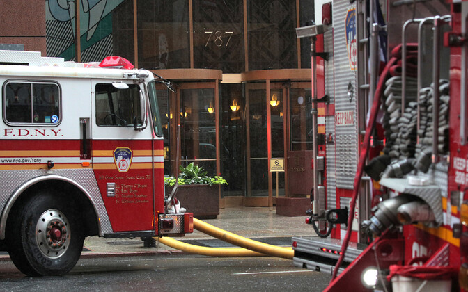 Päästeautod hoone juures, mille katusele helikopter kukkus.