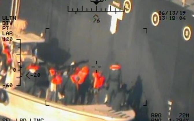 USA kaitseministeeriumi foto Iraani patrullalusest, millel olevad isikud võtavad tankerilt maha plahvatamata magnetmiini.
