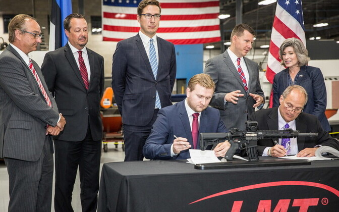 Priit Soosaar (seated, left) and LMT CEO Karl Lewis signing Tuesday's procurement deal in Davenport, Iowa, while Sen. Joni Ernst (R-Iowa) and Estonian ambassador to the US Jonatan Vseviov (standing, second from right), and other representatives, look on.