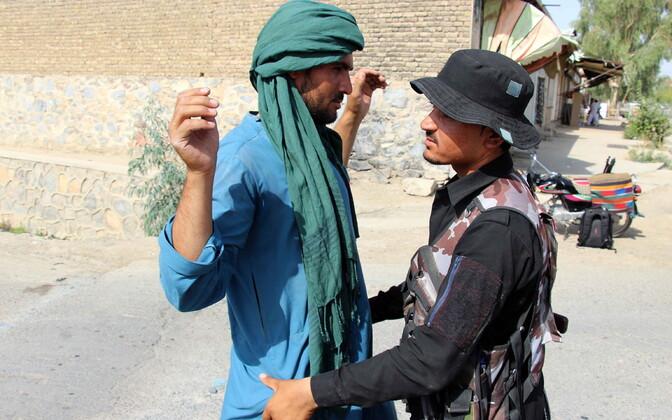 Turvatöötaja Kandahari kontrollpunktis mööduvaid inimesi läbi katsumas.