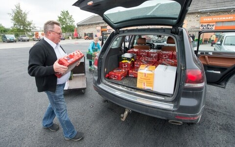 A Finnish tourist loading alcohol into the vehicle in the parking lot of an alcohol store near the Port of Tallinn.