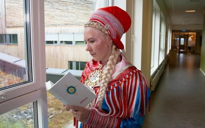 Saami rahvariietes naine uut piiblit lugemas.