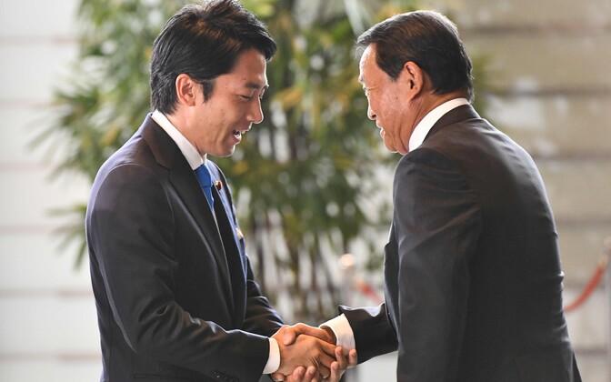 Värske keskkonnaminister Shinjiro Koizumi surub kätt asepeaministril ja rahandusministril Taro Asol