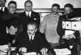 Vjatšeslav Molotov annab allkirja NSV Liidu – Saksamaa sõpruse- ja piirilepingule, Stalini kõrval paremal tema tõlk Vladimir Pavlov. 29. september 1939, varahommik.