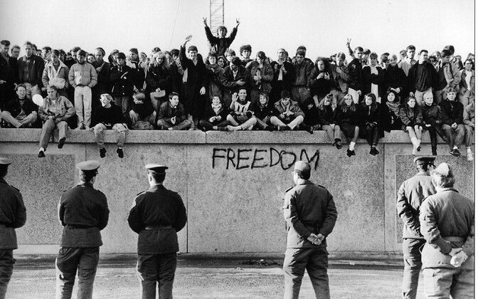 East German students sitting atop the Berlin Wall while West German officials look on.