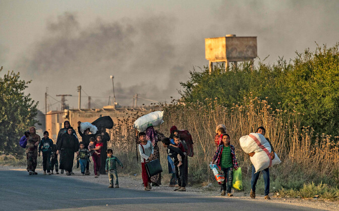 Civilians fleeing Ras al-Ain, Syria, which has been trapped by Turkish air strikes.
