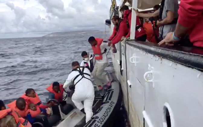 Migrants at sea being helped by a rescue boat.