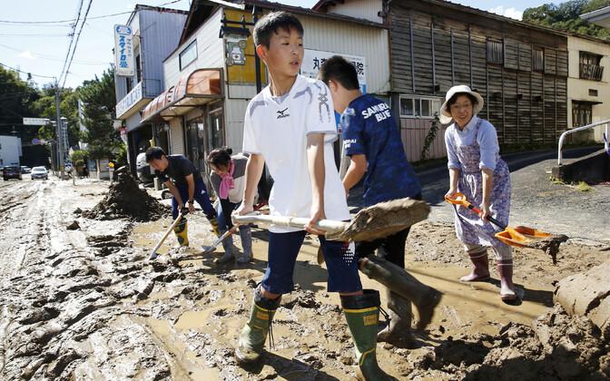 Жители японского города чистят улицы от ила после вызванного ураганом наводнения.