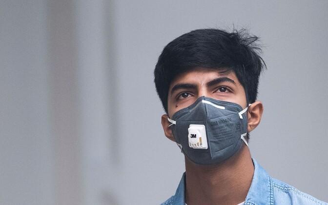 Kaitsvat maski kandev noormees.