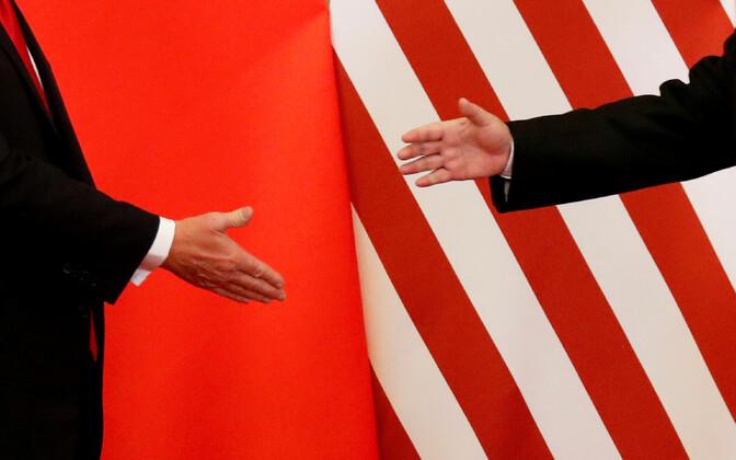 USA ja Hiina liidrite käed kahe maa lippude taustal.