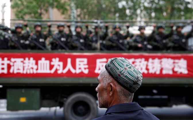 Uiguuri mees vaatamas Ürümqis Hiina julgeolekujõudude sõidukit.