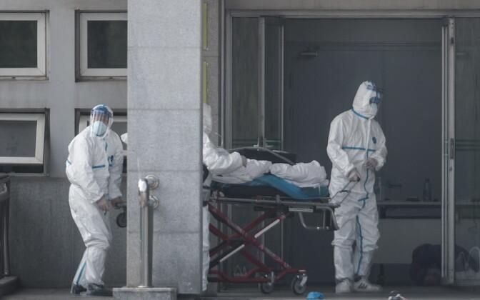 Wuhani meditsiinitöötajad uue viirusega patsienti haiglaravile transportimas.