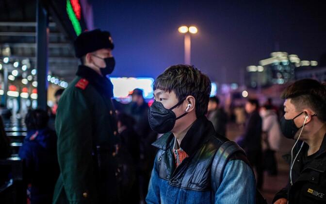 Люди в защитных масках на железнодорожной станции в Пекине.