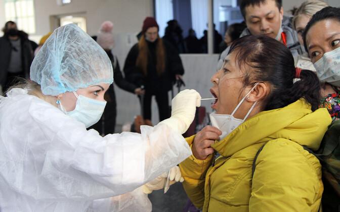 Vene terviseametnikud kontrollivad piiril Hiinast saabuvaid inimesi.