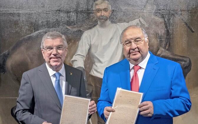 Venemaa miljardär Ališer Usmanov (paremal) annetas Pierre de Coubertini manifesti olümpiamuuseumile, andes selle üle ROK-i presidendile Thomas Bachile.